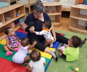 A woman with a hand puppet talking to a group of toddlers sitting in a circle and looking up at her. One toddler is hugging her.