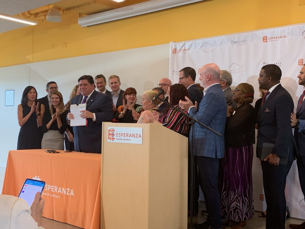 governer pritzker holding a just-signed bill as the people around him applaud.
